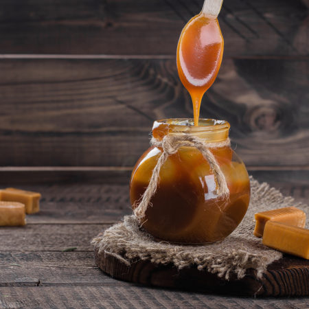 Homemade salted caramel sauce in jar on rustic wooden table background. Copy space.